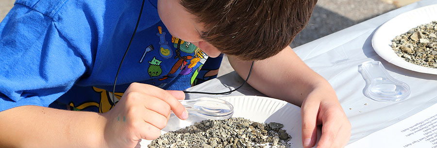 A student searches through a small pile of gravel for fossils using a magnifying glass.